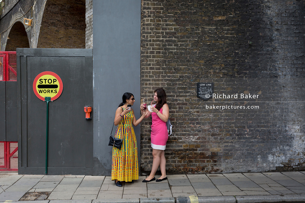 Two women talk beneath the brick wall of a railway arch near Borough Market, on 6th September, in London, England.
