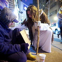 """Michael Grant, 28, """"Philly Jesus,"""" prays with a beggar in Philadelphia, PA.  Nearly everyday for the last 8 months, Grant has dressed as Jesus Christ, and walked the streets of Philadelphia to share the Christian gospel by example.  He quickly acquired the nickname of """"Philly Jesus,"""" which he has gone by ever since."""