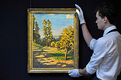 """© Licensed to London News Pictures. 17/11/2017. London, UK.  London, UK.  17 November 2017. A technician presents """"Landscape with Two Trees"""", 1922, by Sir Winston Churchill (Est. GBP 100-150k).  Preview upcoming auctions of Modern & Post War British Art and Scottish Art taking place at Sotheby's, New Bond Street, on 21 and 22 November. Photo credit: Stephen Chung/LNP"""
