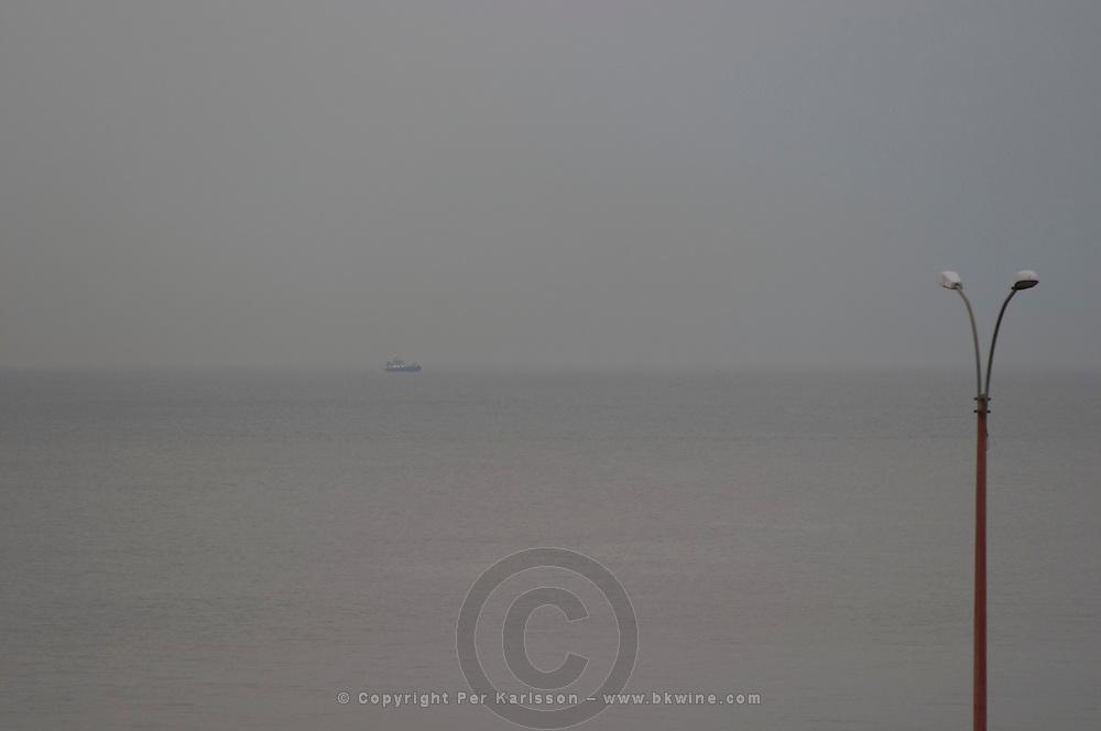 A view over the Rio de la Plata in Montevideo on a rainy day, fog rain and haze making it a gray day, a ship on the horizon and a lamp post Rambla sur and Rambla Gran Bretagna along the River Rio de la Plata Montevideo, Uruguay, South America