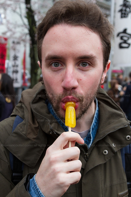 A western man licks a penis shaped lollipop during the Kanamara Matsuri, (Festival of the Steel Phallus). Kawasaki Daishi, Kanagawa, Japan. Sunday April 3rd 2016. The famous Kawasaki Penis Festival started in 1977 as a small festival to celebrate an old legend about the defeat of a penis eating demon. Today the festival is a huge draw for Japanese and foreign tourists and raises money for HIV and AIDS research.