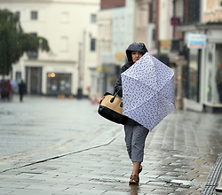 people under umbrellas near Windsor Castle as a yellow weather warning for rain has been issued for parts of the UK.
