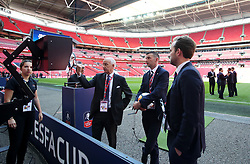Match referee Michael Oliver (centre) examines the VAR technology by the touchline before the game