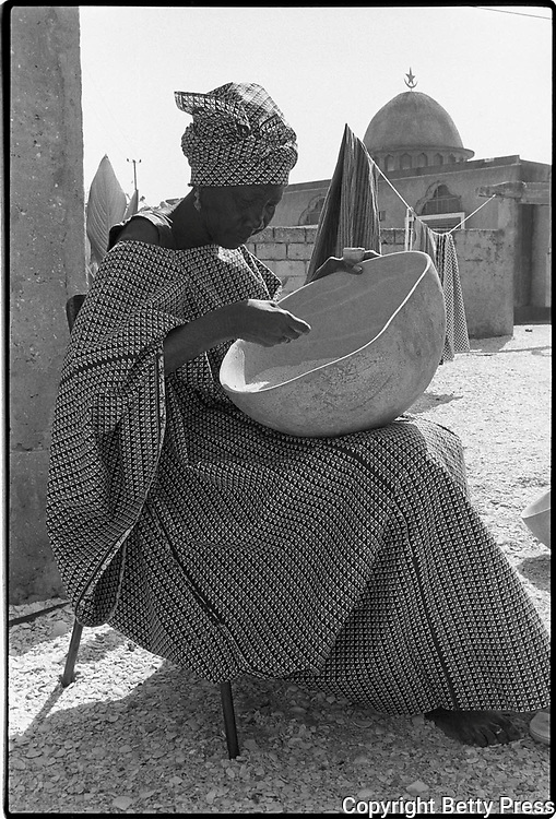 A calabash with holes cannot be filled. Kenyan proverb<br /> <br /> While visiting a women's group that was setting up a dried fish business, I saw this woman sitting in a courtyard cleaning rice. As she was doing this most mundane job, she was beautifully dressed and so composed that even having her picture taken did not distract her from her work. Cleaning rice, Mbao, Senegal  1988