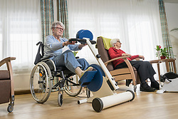 Two senior woman exercising on exercise bike in rest home
