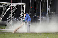 Middletown, New York - Middletown athletic director David Coates spreads a drying agent on the field after a  New York State Class B boys' soccer semifinal game at Faller Field on Nov. 17, 2012. The championship games were played the following day.