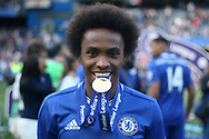 Willian of Chelsea takes a bite out of his winners medal. Premier league match, Chelsea v Sunderland at Stamford Bridge in London on Sunday 21st May 2017.<br /> pic by Steffan Bowen,  Andrew Orchard sports photography.