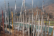 Prayer flags above the town and district center of Wangdi Phodrang. Buddhist prayers are imprinted onto flags that are attached to tall hand hewn poles. The prayers are said to disperse into the winds for the protection of people living or dead. Some are wind flags, which are erected on mountaintops and hillsides for personal wishes on behalf of the erector. Others are prayer flags, which are erected by families to cleanse the sins of their deceased family members. From coverage of revisit to Material World Project family in Bhutan, 2001.