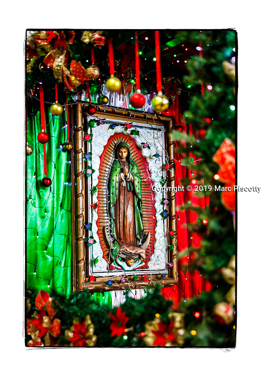 SHOT 2/20/19 10:53:46 AM -  A corner capilla hidden behind crates of fruit inside a fruit stand in the Mercado Municipal Lucas de Gálvez in Merida, Mexico. The capillas are often dedicated to certain patron saints, such as Nuestra Senora de Guadalupe. Our Lady of Guadalupe is a powerful and ubiquitous symbol of Mexican identity because some guess that Our Lady of Guadalupe's skin tone matches that of Mexico's indigenous population: light brown. She is as much revered for her striking similarity to the vanquished native Mexican population as she is for being the mother of God. Often times they contain prayer candles, pictures, personal artifacts or notes. Mérida is the capital and largest city in Yucatan state in Mexico, as well as the largest city of the Yucatán Peninsula. As the largest city in the Yucatan it has become a hub for commerce and culture. (Photo by Marc Piscotty / © 2019)