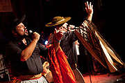 Brazilian Gaucho men in traditional dress singing passionately on stage, Reponte da Cancao music festival and song competition in Sao Lorenzo do Sul, RIo Grande do Sul, Brazil.