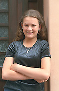Girl age 17 smiling in doorway with arms folded.  Torun Poland