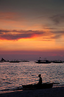 Boats silhouetted agains a beautiful sunset on the waters off White Sand Beach, Boracay, Philippines.