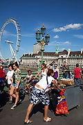 Tourists cross Westminster bridge by the River Thames at Westminter, London. A hot dog seller pushes her hotdog stand. With the iconic London Eye behind this is one of the busiest areas for tourism in the city.