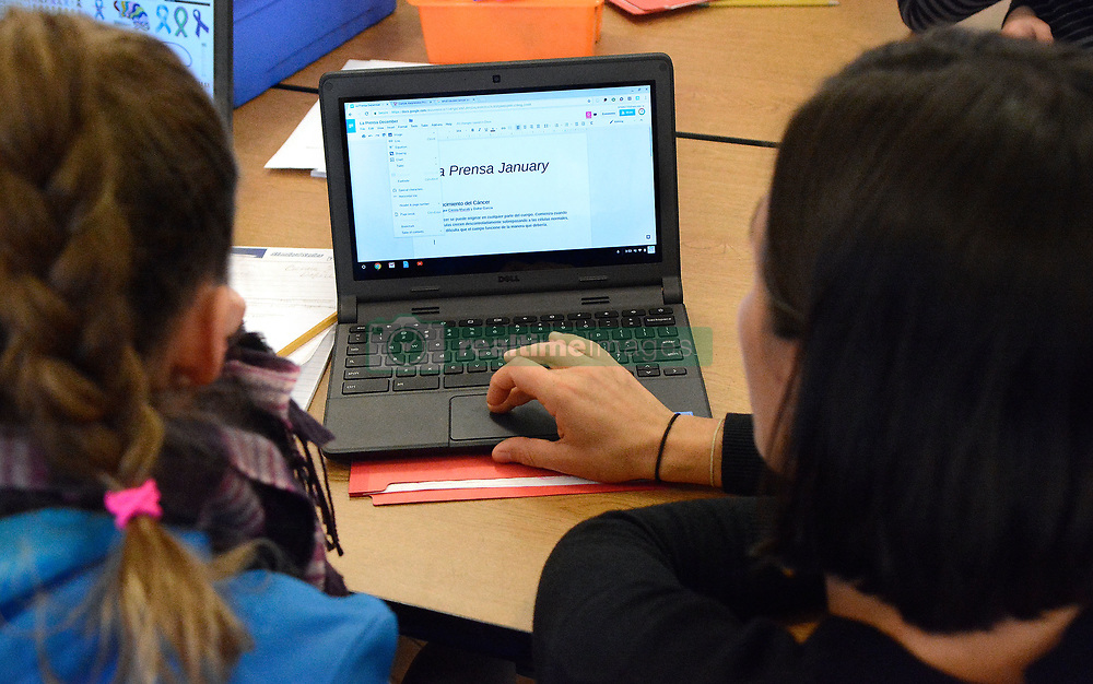 January 18, 2018 - Albuquerque, NM, U.S. - Newspaper advisor and teacher Lauren Gutierrez(right) helps one of her reporters Cienna Mazotti on her laptop as she works on a story for La Prensa, a dual language newspaper writer and published at Coronado Elementary School, a dual language school in downtown Albuquerque.  Thursday Jan. 18, 2018. (Credit Image: © Jim Thompson/Albuquerque Journal via ZUMA Wire)