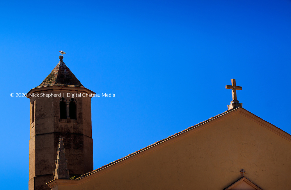 A seagull atop a church tower and roof with a crucifix in Ibiza Town, Balearic Islands, Spain.