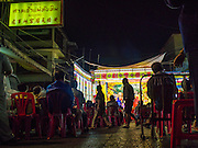 16 JANUARY 2015 - BANGKOK, THAILAND: Spectators walk into the Sai Yong Hong Opera Troupe performance at the Chaomae Thapthim Shrine, a Chinese shrine in a working class neighborhood of Bangkok near the Chulalongkorn University campus. The troupe's nine night performance at the shrine is an annual tradition and is the start of the Lunar New Year celebrations in the neighborhood. Lunar New Year, also called Chinese New Year, is officially February 19 this year. Teochew opera is a form of Chinese opera that is popular in Thailand and Malaysia.    PHOTO BY JACK KURTZ