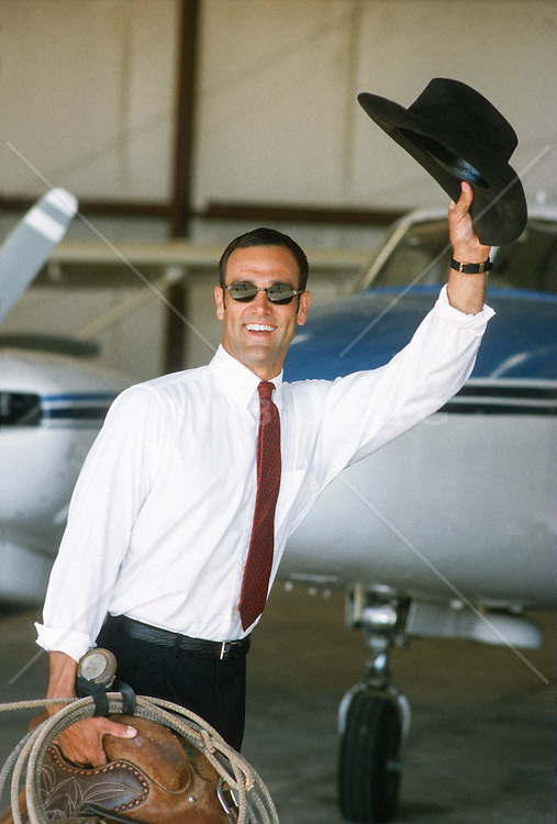 cowboy in a shirt and tie in an airplane hanger waving goodbye