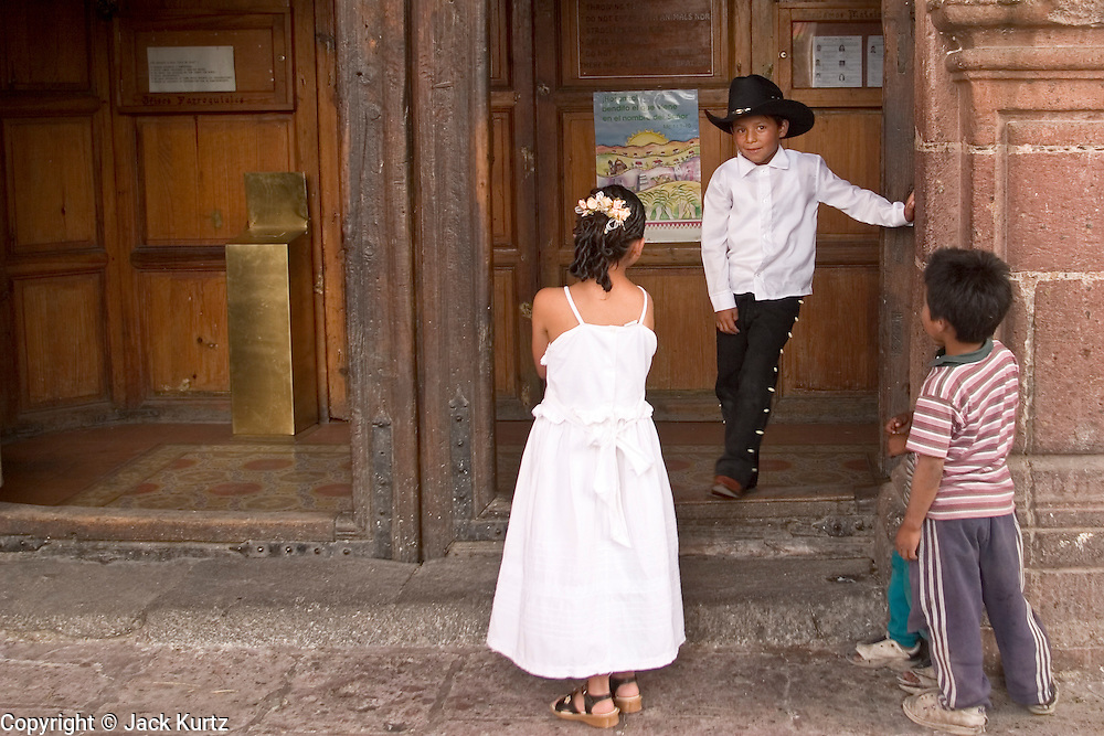 03 APRIL 2004 - SAN MIGUEL DE ALLENDE, GUANAJUATO, MEXICO: Children play in front of the church during a wedding at the Iglesia Parroguia, the principal Catholic church in San Miguel de Allende, Mexico. San Miguel, which was founded in the 1600s, is one of Mexico's premier colonial cities. It has very strict zoning and building codes meant to preserve the historic nature of the city center. About 7,500 US citizens, mostly retirees, live in San Miguel. PHOTO BY JACK KURTZ