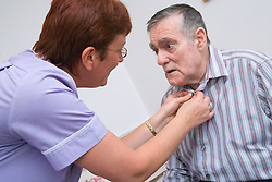Care Assistant of a Nursing Home buttoning the shirt of a man with Alzheimer's Disease,