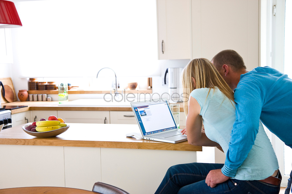 Back View of Couple Using Laptop in Kitchen