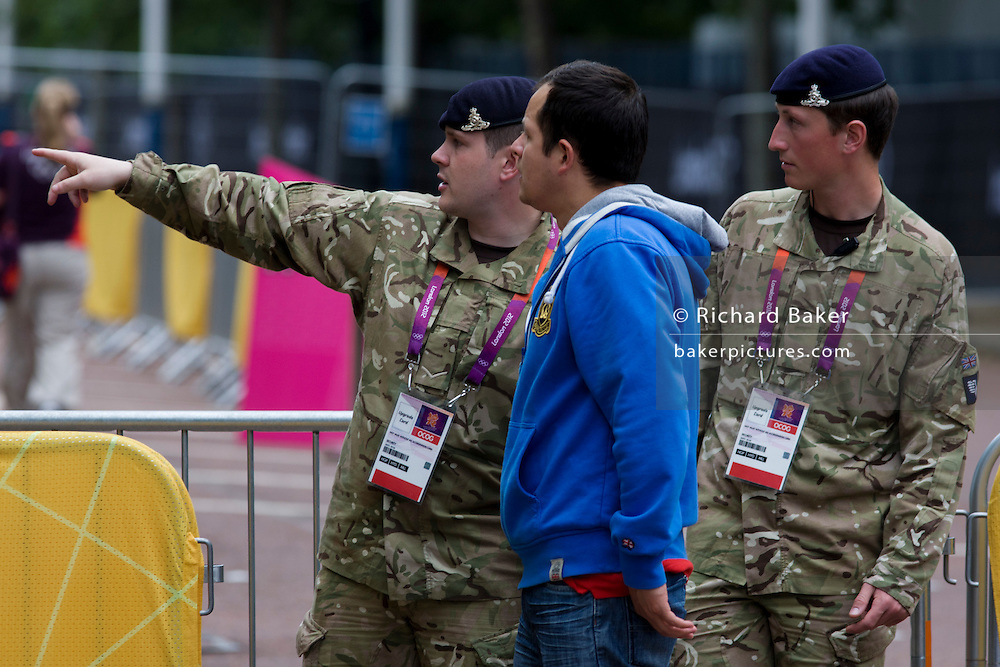 Soldiers of the Royal Artillery regiment in British army direct spectators while standing guard the entrance to the volleyball venue in central London next to the IOC rings logo on day 4 of the London 2012 Olympic. A total of 18,000 defence personel were called upon to make the Games secure following the failure by security contractor G4S to provide enough private guards. The extra personnel have been drafted in amid continuing fears that the private security contractor's handling of the £284m contract remains a risk to the Games.