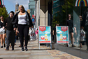 A woman carrying a supermarket shopping bag walks past a sale sign with a young boy in tow on 26th August, 2021 in Manchester, United Kingdom. Many of the UKs high streets and shopping centres are bustling once again, welcoming shoppers back as footfall slowly climbs back to levels seen before the restrictions brought about by the Covid-19 pandemic.