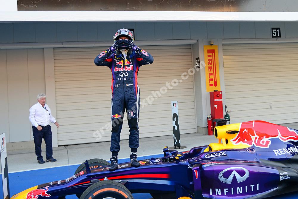 Sebastian Vettel (Red Bull-Renault) celebrates in parc ferme after the 2013 Japanese Grand Prix in Suzuka. Also in the picture: FIA official Herbie Blash. Photo: Grand Prix Photo