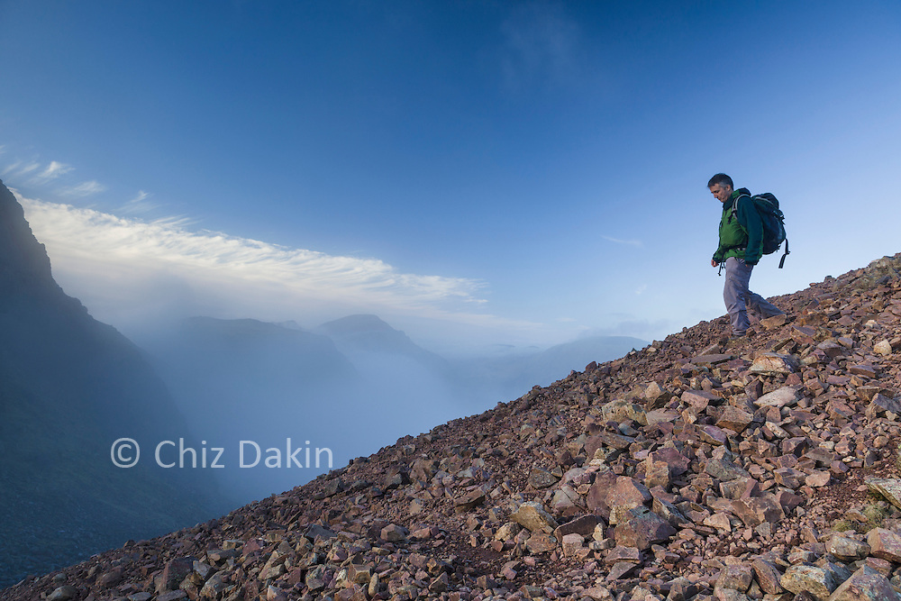 Walker descending scree slope to Windy Gap (between Green Gable and Great Gable, Cumbria)