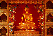 The Buddha seen as part of a shrine in the prayer room of Kagyu Samye Ling Buddhist retreat centre in Eskdalemuir, Scotland. A Buddhist shrine provides a focal point for Buddhists when they are meditating, practising puja (worship) and for gatherings of Buddhists studying together. Shrines can vary from a small, simple shrine in the home or garden of a Buddhist, through to the large, ornate shrines or temples found across the globe. At the Samye Ling monastery, most visitors are westerners in this peaceful location for spiritual cleansing and often to find answers to their complicated, modern lives. And many here have had a troubled youth and are sometimes escaping a criminal past, who arrive in the Scottish wilderness for isolated retreat periods, for short-term spiritual relaxation.