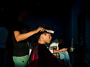 """14 FEBRUARY 2019 - SIHANOUKVILLE, CAMBODIA:  A Chinese man who works in a casino gets a haircut at a Chinese barbershop in Sihanoukville. There are thousands of Chinese workers in Sihanoukville who work to support the casino and hotel industry in the town and thousands of other Chinese migrants have moved into Sihanoukville and opened businesses that cater to the workers. There are about 80 Chinese casinos and resort hotels open in Sihanoukville and dozens more under construction. The casinos are changing the city, once a sleepy port on Southeast Asia's """"backpacker trail"""" into a booming city. The change is coming with a cost though. Many Cambodian residents of Sihanoukville  have lost their homes to make way for the casinos and the jobs are going to Chinese workers, brought in to build casinos and work in the casinos.      PHOTO BY JACK KURTZ"""
