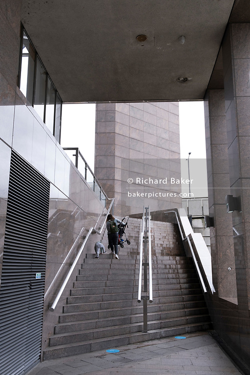 An adult carries a child's buggy alongside a toddler up steep steps that rise beneath an office building at London Bridge, on 24th May 2021, in London, England.