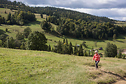 With the Slovakian border on the distant forested ridge, a lady walker climbs uphill from Biala Woda in southern Poland, on 20th September 2019, Biala Woda, Jaworki, near Szczawnica, Malopolska, Poland.