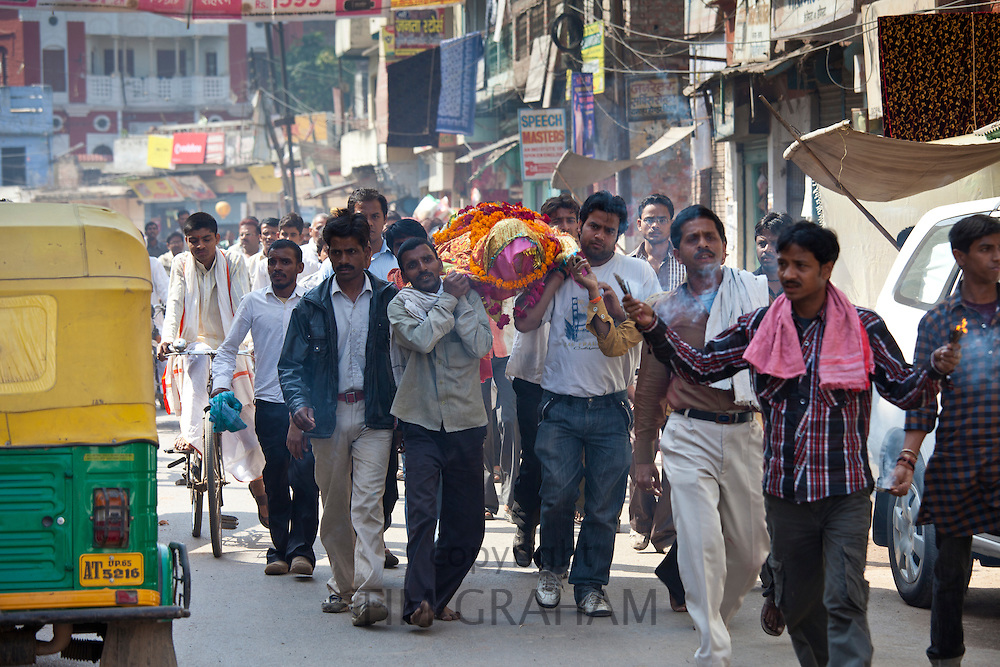 Body of dead Hindu woman carried in procession in street for funeral pyre cremation by the Ganges, Varanasi, India