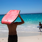 Locals rie the waves on a white sand beach on Hawaii.