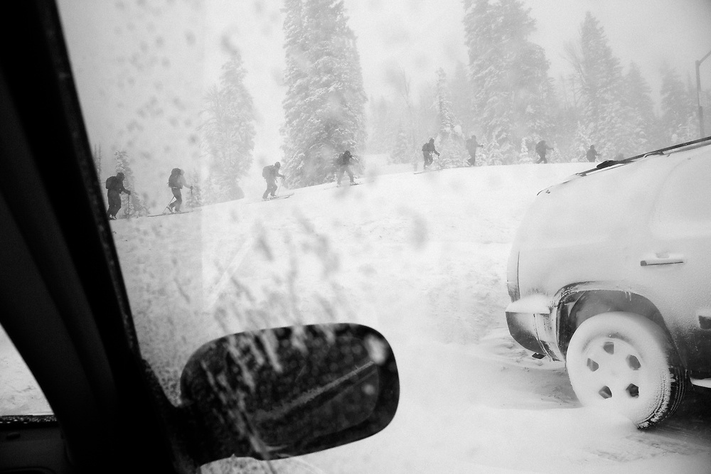 A group of Bridger-Teton Avalanche forecasters skin by the parking lot on the top of Teton Pass.