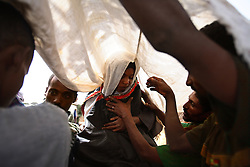 Family members place a white cloth over the head of Leyualem, 14, as she is prepared to be wisked away on a mule by her new groom and groomsmen in the Amhara Region, Ethiopia on May 23, 2007.  Leyualem had never met her husband before her wedding day, yet sumitted as they bound her in the white wedding cloth. The men later said it was placed over her head so she would not be able to find her way back home, should she want to escape the marriage.