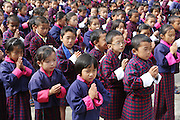 School children assembly at Wangdue Chhoeling Lower Secondary School, Bumthang, Bhutan..Bhutan the country that prides itself on the development of 'Gross National Happiness' rather than GNP. This attitude pervades education, government, proclamations by royalty and politicians alike, and in the daily life of Bhutanese people. Strong adherence and respect for a royal family and Buddhism, mean the people generally follow what they are told and taught. There are of course contradictions between the modern and tradional world more often seen in urban rather than rural contexts. Phallic images of huge penises adorn the traditional homes, surrounded by animal spirits; Gross National Penis. Slow development, and fending off the modern world, television only introduced ten years ago, the lack of intrusive tourism, as tourists need to pay a daily minimum entry of $250, ecotourism for the rich, leaves a relatively unworldly populace, but with very high literacy, good health service and payments to peasants to not kill wild animals, or misuse forest, enables sustainable development and protects the country's natural heritage. Whilst various hydro-electric schemes, cash crops including apples, pull in import revenue, and Bhutan is helped with aid from the international community. Its population is only a meagre 700,000. Indian and Nepalese workers carry out the menial road and construction work.