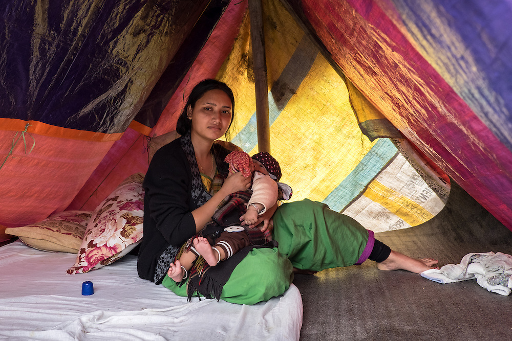 Devastating April 2015 Nepal Earthquake. Panga Village, Kirtipur, Kathmandu Valley. A woman feeding  her baby in a tent camp set up in an open field. Out of fear of new quakes, the days after the earthquake struck everybody slept outside of their homes. More than a third of the houses in Panga were destroyed, most of them old traditional houses made of brick.