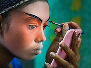 15 OCTOBER 2015 - BANGKOK, THAILAND: A Chinese opera performer works on her eye make up before performing at the Vegetarian Festival at the Joe Sue Kung Shrine in the Talat Noi neighborhood of Bangkok. The Vegetarian Festival is celebrated throughout Thailand. It is the Thai version of the The Nine Emperor Gods Festival, a nine-day Taoist celebration beginning on the eve of 9th lunar month of the Chinese calendar. During a period of nine days, those who are participating in the festival dress all in white and abstain from eating meat, poultry, seafood, and dairy products. Vendors and proprietors of restaurants indicate that vegetarian food is for sale by putting a yellow flag out with Thai characters for meatless written on it in red. The shrine is famous for the Chinese opera it hosts during the Vegetarian Festival. The operas are free.    PHOTO BY JACK KURTZ