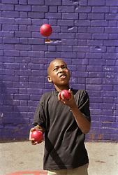 Young boy juggling balls,