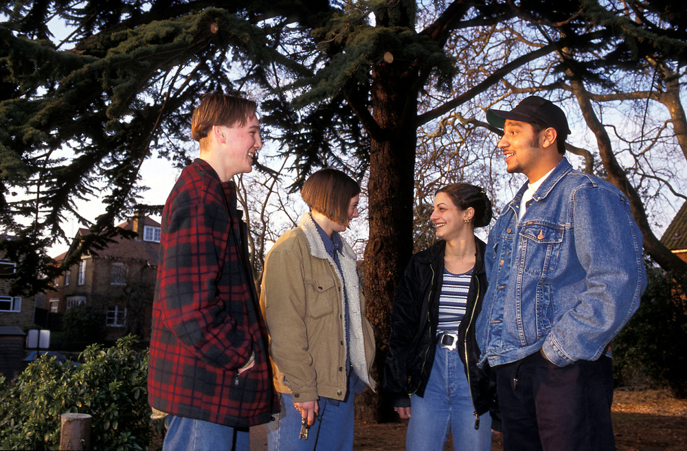 A group of university students  hanging around chatting on campus,
