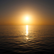 The sun approaches the horizon on a very clear and calm day over the water. Taken at Swains Reef on the southern end of the Great Barrier Reef of the coast of Queensland, Australia.