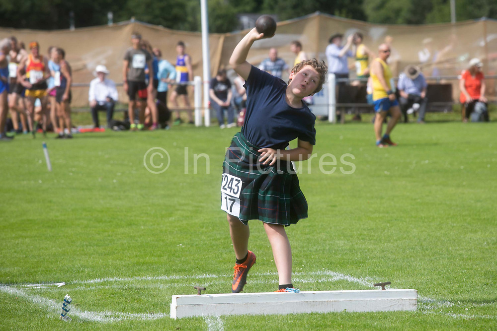 Highland Games, 3rd of August 2019, Newtonmore, Scotland, United Kingdom. A young boy compete in the shot put competition. The Highland Games is a traditional annual event where competitors compete as strong men, runners, dancers, pipers and at tug-of-war. The games go back centuries and are happening through-out the summer across Scotland. The games are both an important event locally and a global tourist attraction.