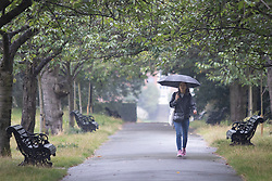 © Licensed to London News Pictures. 19/09/2021. London, UK. A woman shelters under an umbrella during a rain shower in Greenwich Park in South East London. A yellow weather warning for rain is in place for parts of England.  Photo credit: George Cracknell Wright/LNP