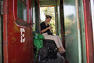 A German woman sits on luggage on a train traveling to Ella, Sri Lanka