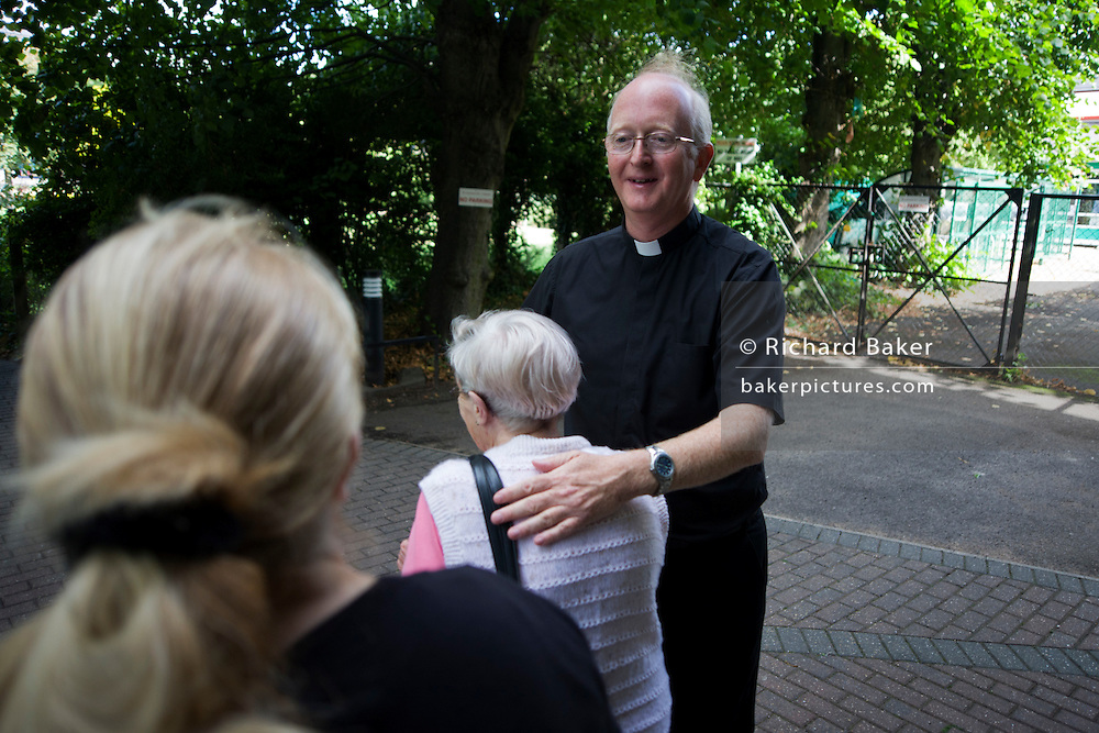 Catholic priest bids goodbye to parishioners after morning Mass at St. Lawrence's Catholic church in Feltham, London.