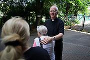 Catholic priest bids goodbye to parishioners after morning Mass at St. Lawrence's Catholic church in Feltham, London.