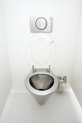 Modern stainless steel toilet bowl and fittings in lavatory cubicle