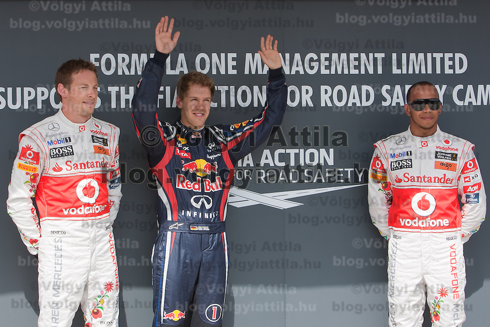 McLaren Formula One driver Jenson Button (L) of Britain, Red Bull Racing Formula One driver Sebastian Vettel (C) of Germany and McLaren Formula One driver Lewis Hamilton (R) of Britain celebrate their victory after the qualifyer of the Hungarian F1 Grand Prix in Mogyorod (about 20km north-east from Budapest), Hungary. Saturday, 30. July 2011. ATTILA VOLGYI