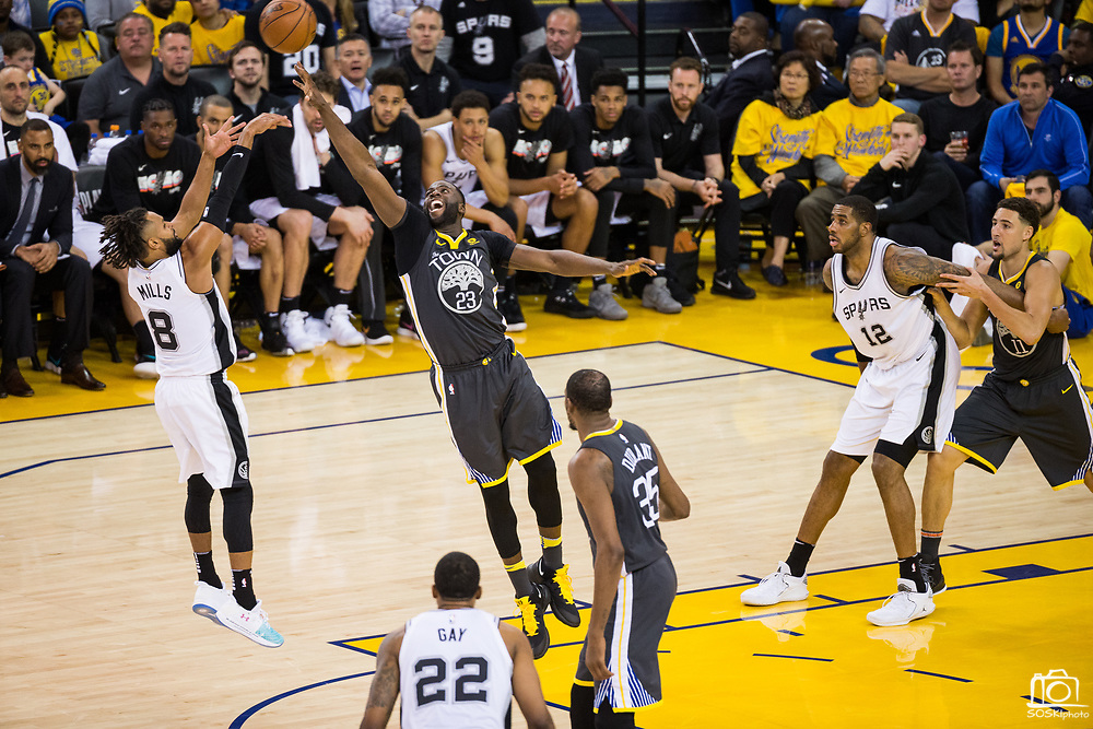 Golden State Warriors forward Draymond Green (23) attempts to block a shot by San Antonio Spurs guard Patty Mills (8) during Game 2 of the Western Conference Quarterfinals at Oracle Arena in Oakland, Calif., on April 16, 2018. (Stan Olszewski/Special to S.F. Examiner)